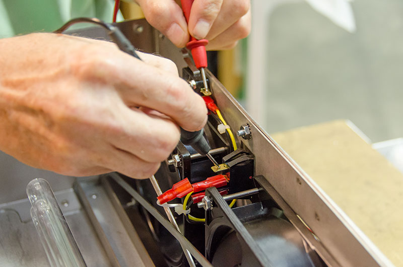 An engineer tests the electrical connections on an enclosure.