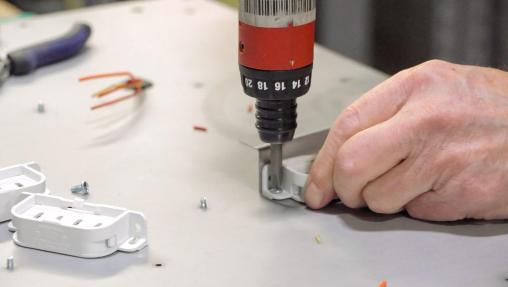 A technician screws in a sub-assembly component.
