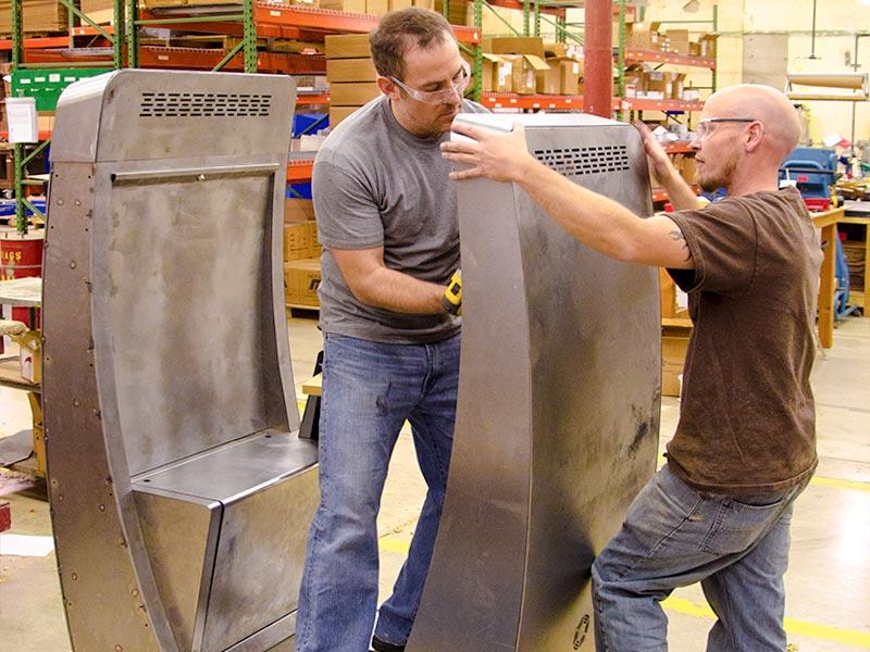 Two workers assemble a sleek health industry kiosk