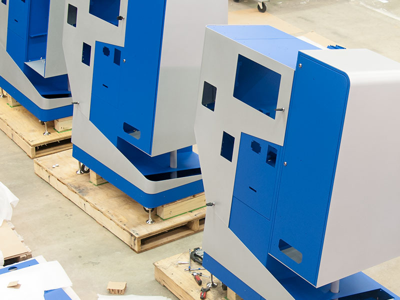 Painted kiosks are placed on palettes before final assembly and packaging.