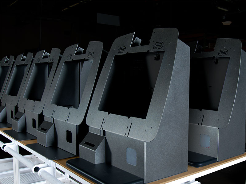 A lineup of security kiosks are assembled and ready for accessory components to be installed.