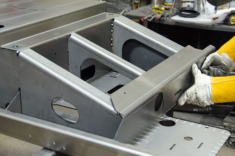 A welding technician lines up a panel on the main assembly.